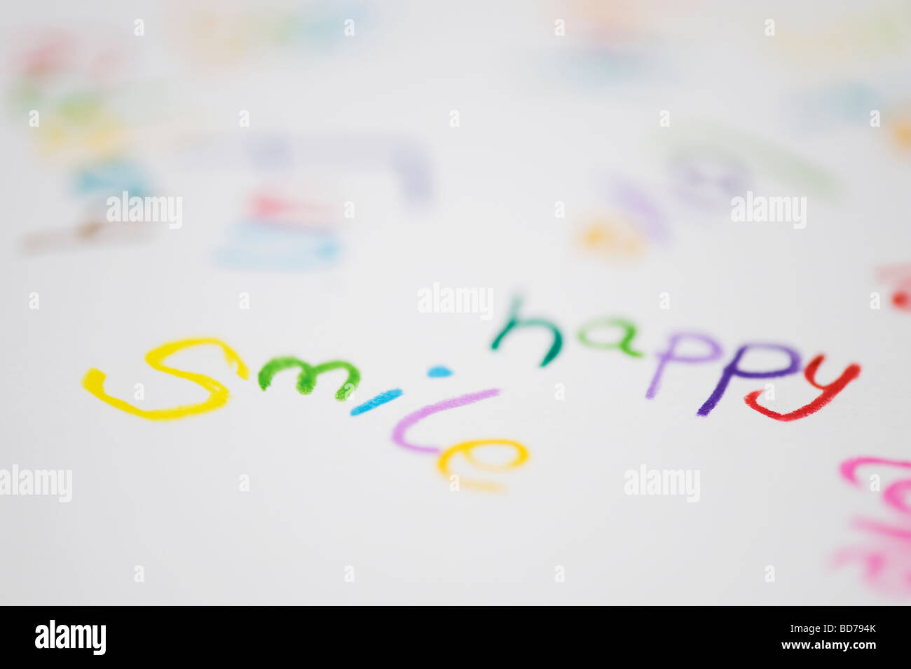 Coloured word smile, happy and love on paper written in colouring pencils - Stock Image
