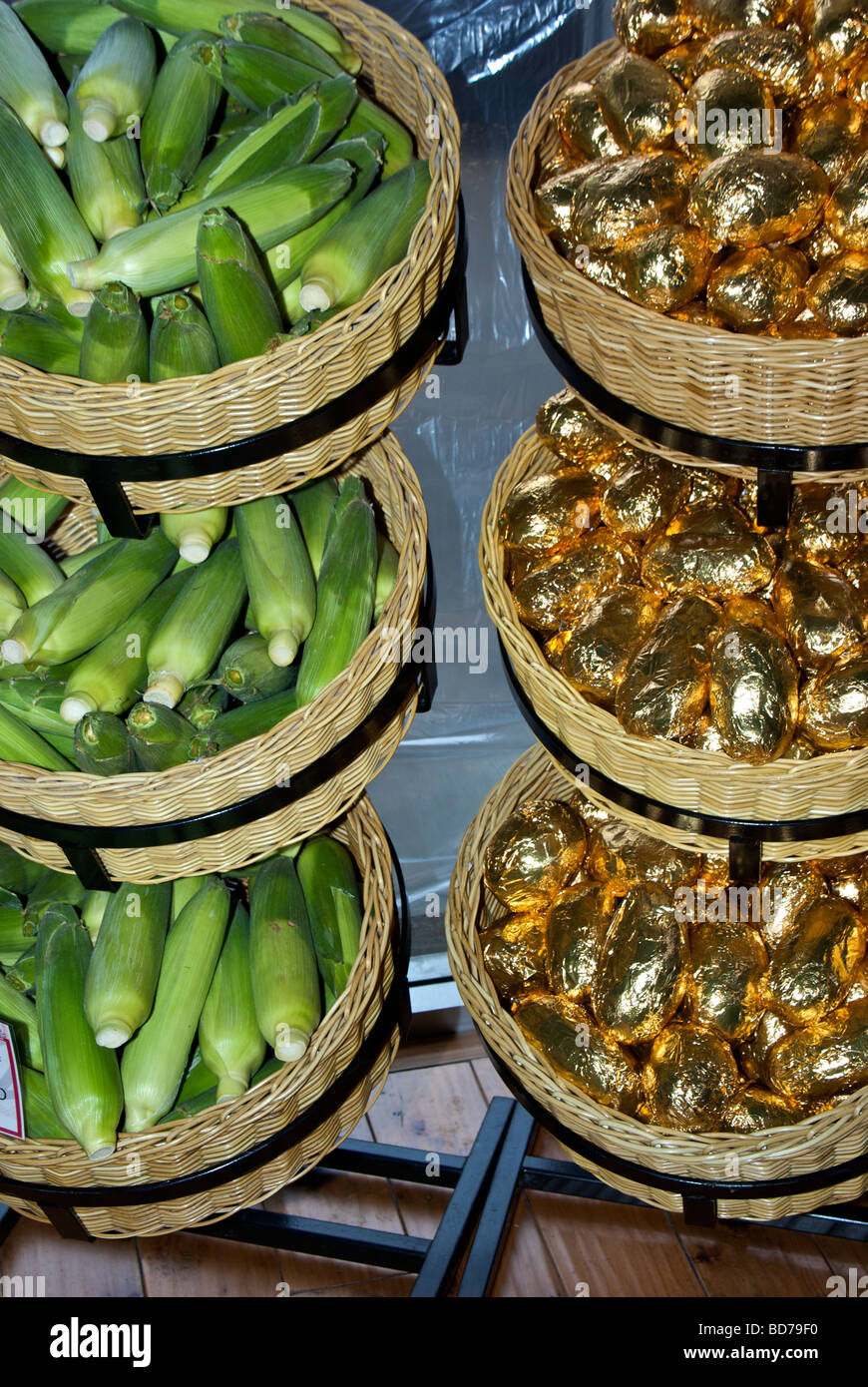 Baskets of jubilee corn and gold foil wrapped baking potatoes at butcher shop - Stock Image