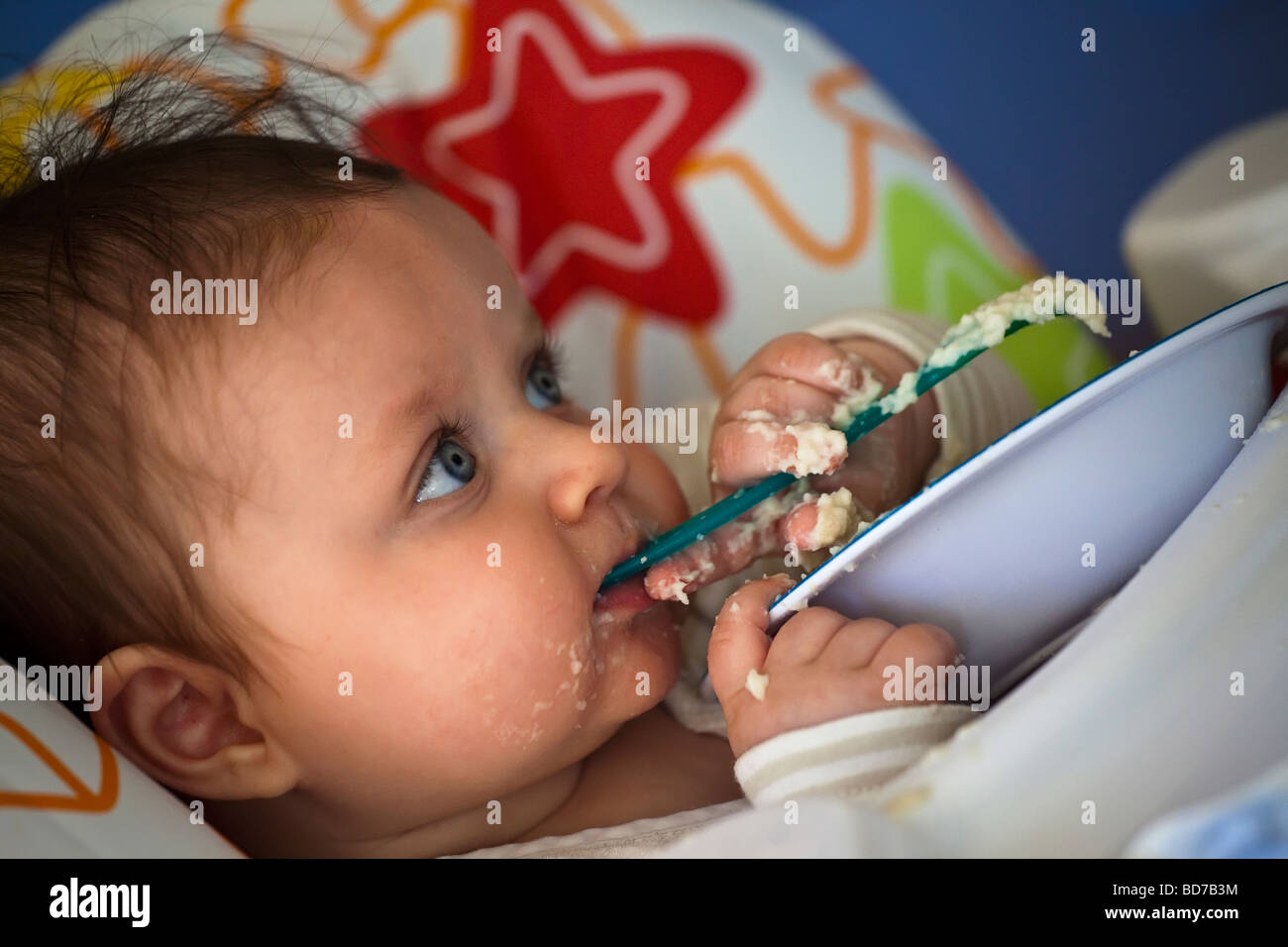 Young baby under six months old spoon feeding and making a mess - Stock Image