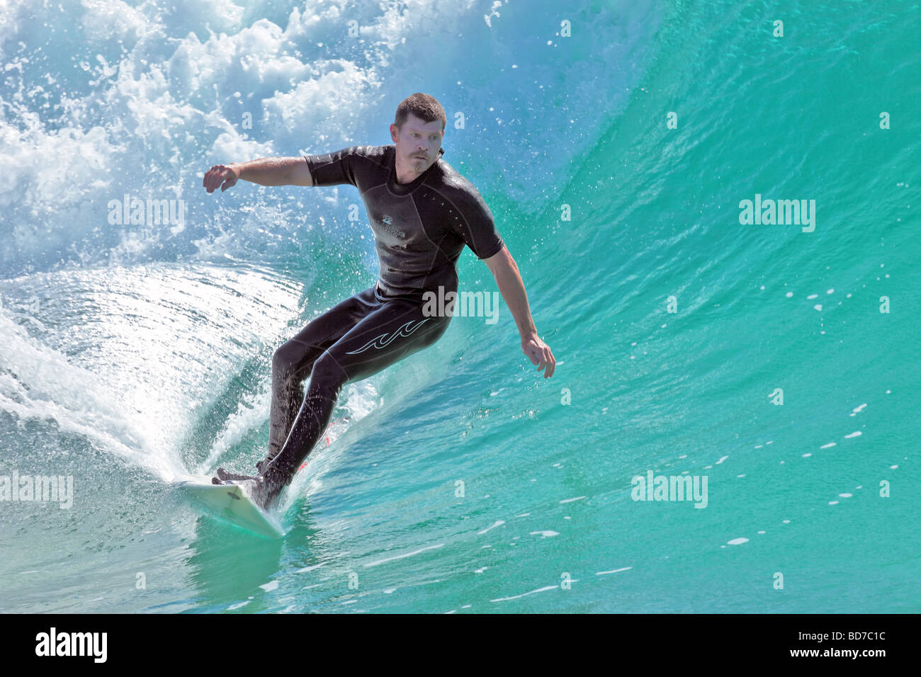 Surfer captures a wave for a ride into the shore late afternoon Stock Photo