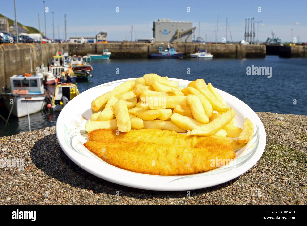 A plate of traditional british fish and chips on the harbour side at Scrabster, Scotland, UK - Stock Image