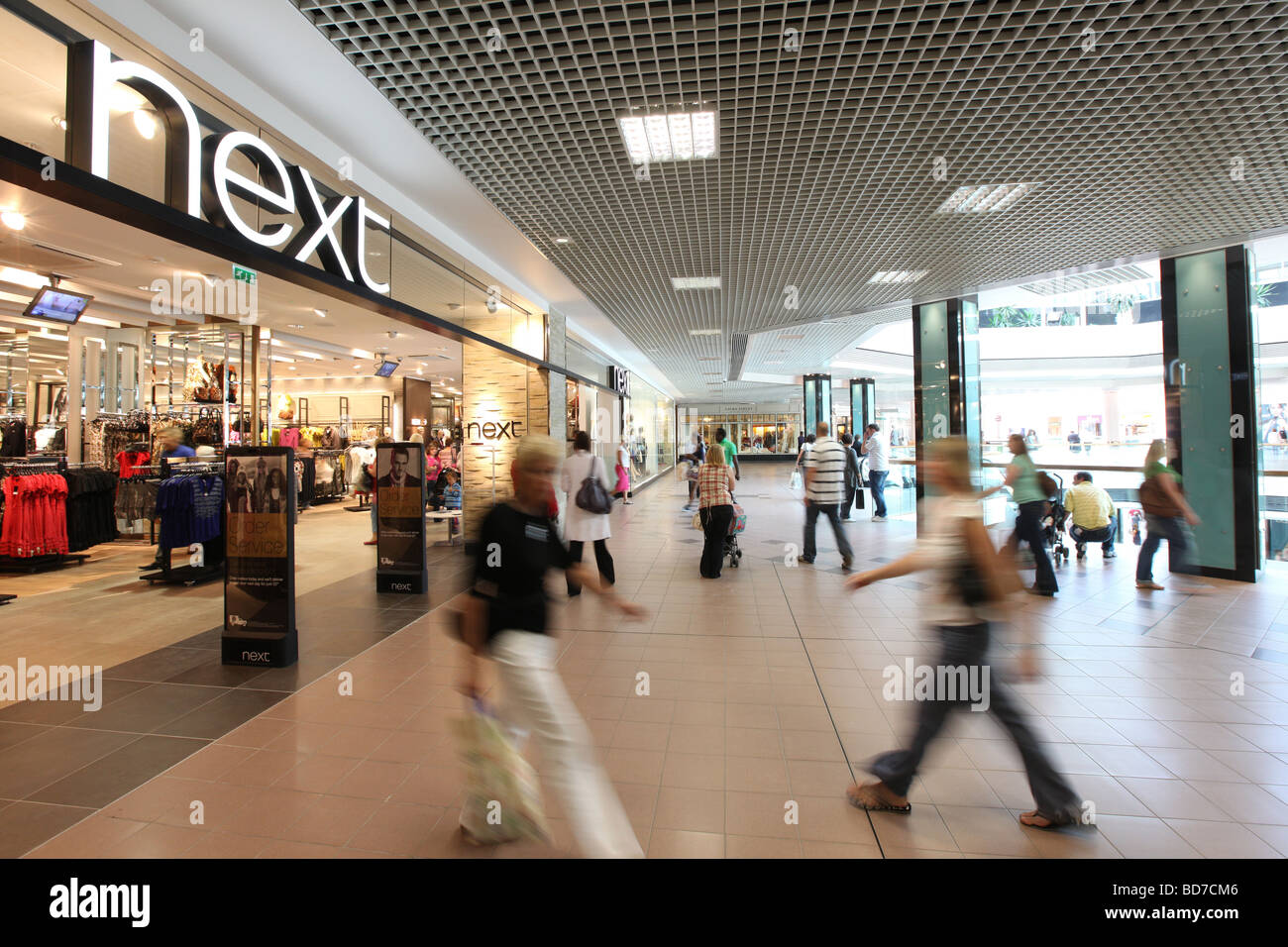 Shoppers at a busy Next store in a shopping centre in the UK - Stock Image