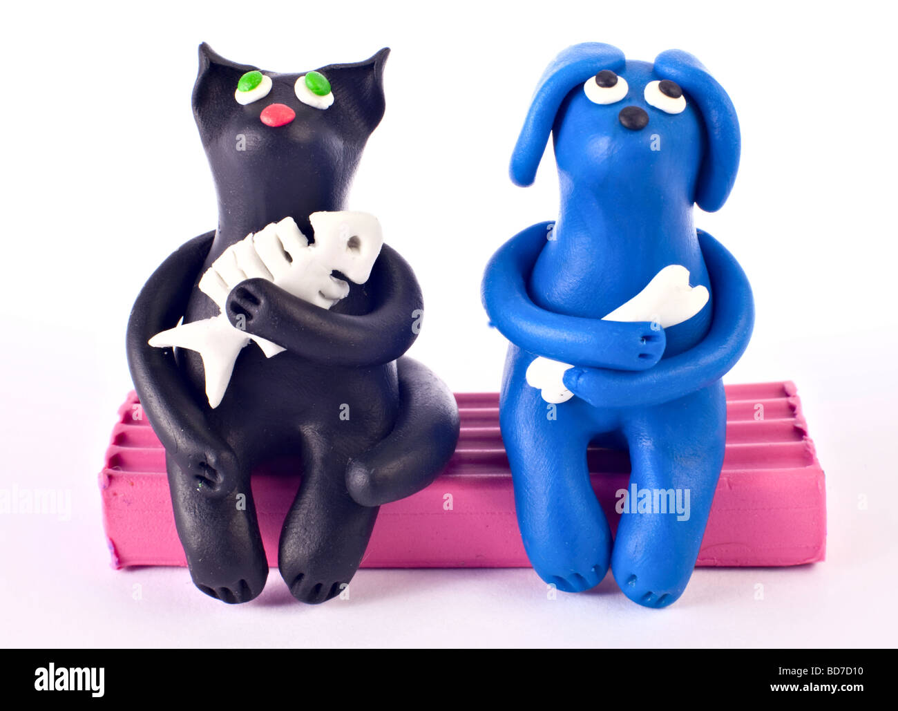 Plasticine cat and dog sitting and dreaming together - Stock Image