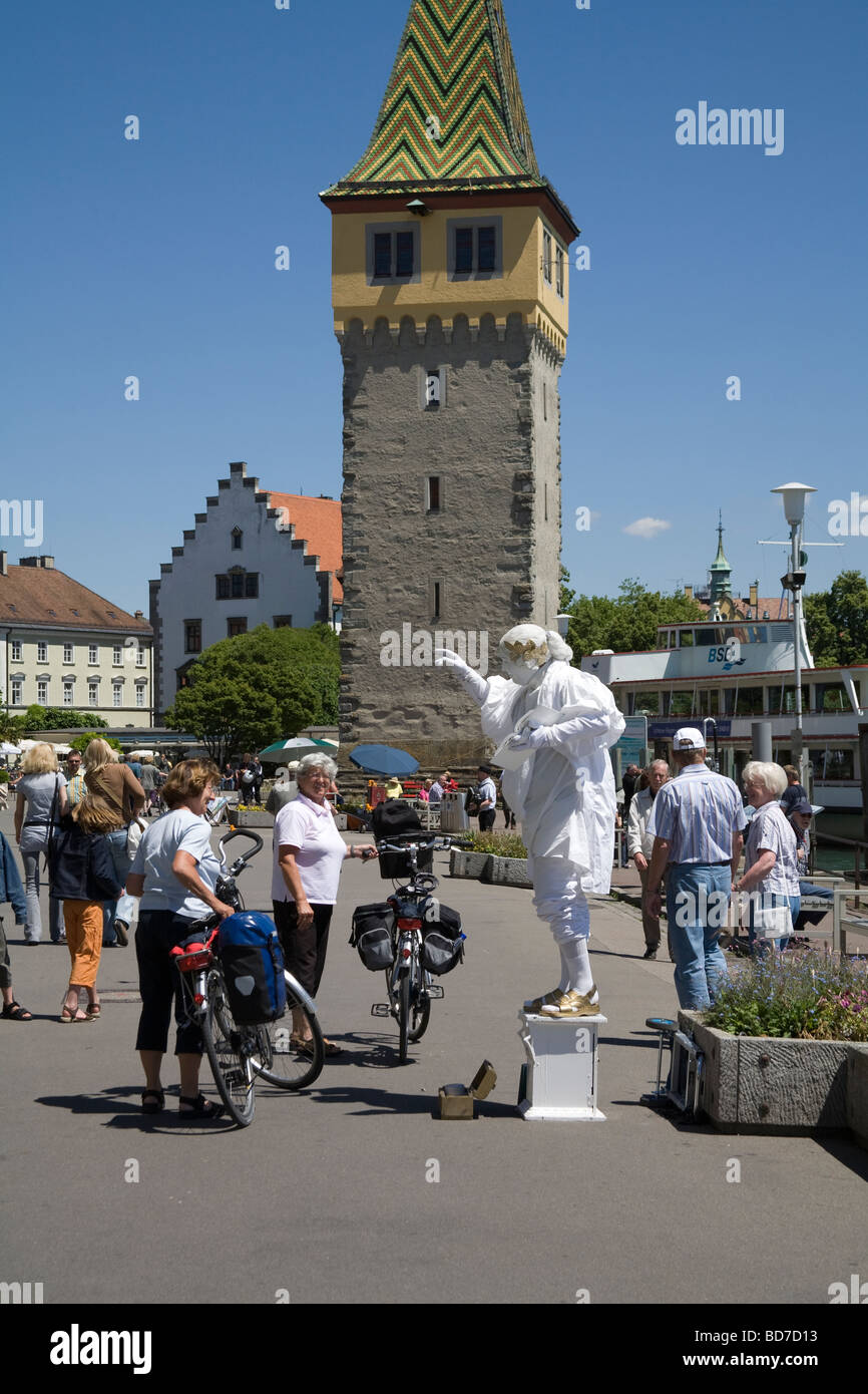 Lindau Bavaria Germany Mime artist performing on wide pedestrianised promenade in front of Mangturm watched by female - Stock Image