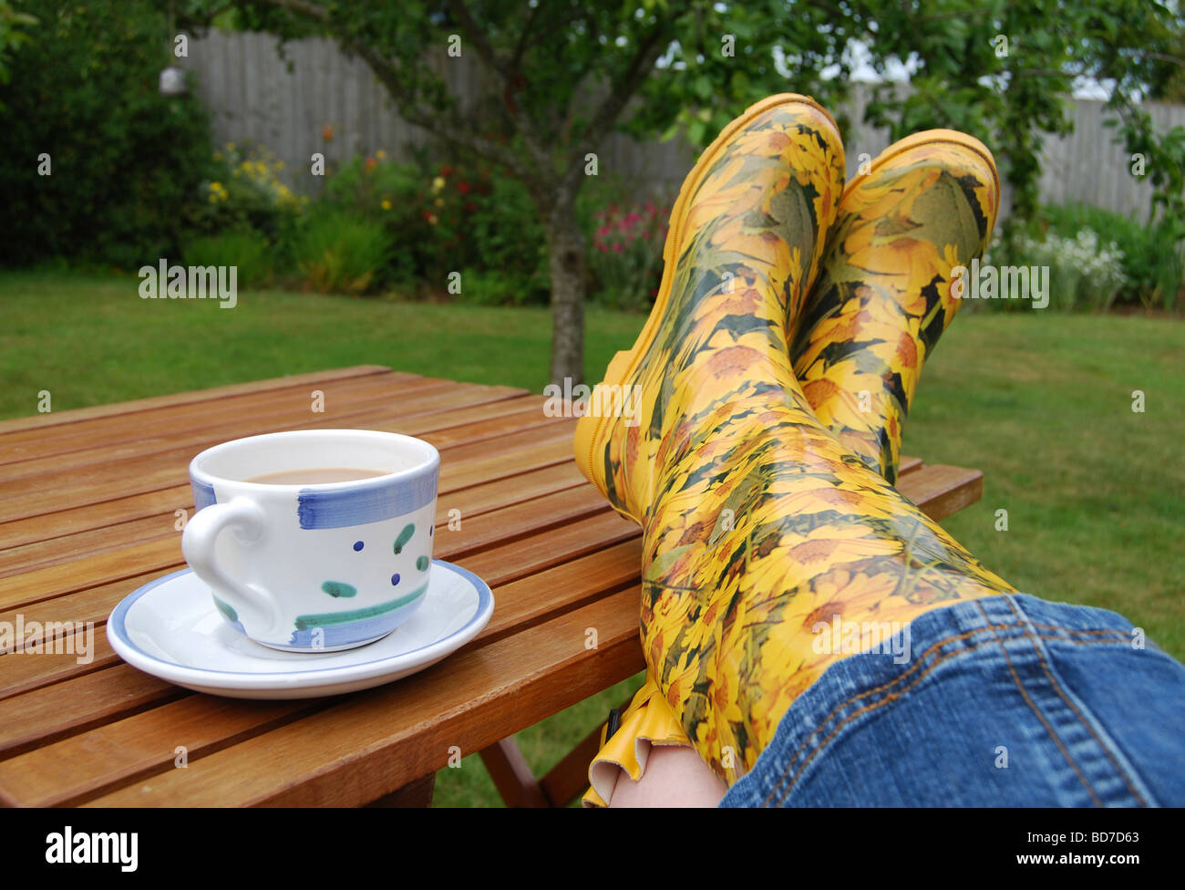A well-earned coffee break for the gardener and her yellow wellies! Stock Photo