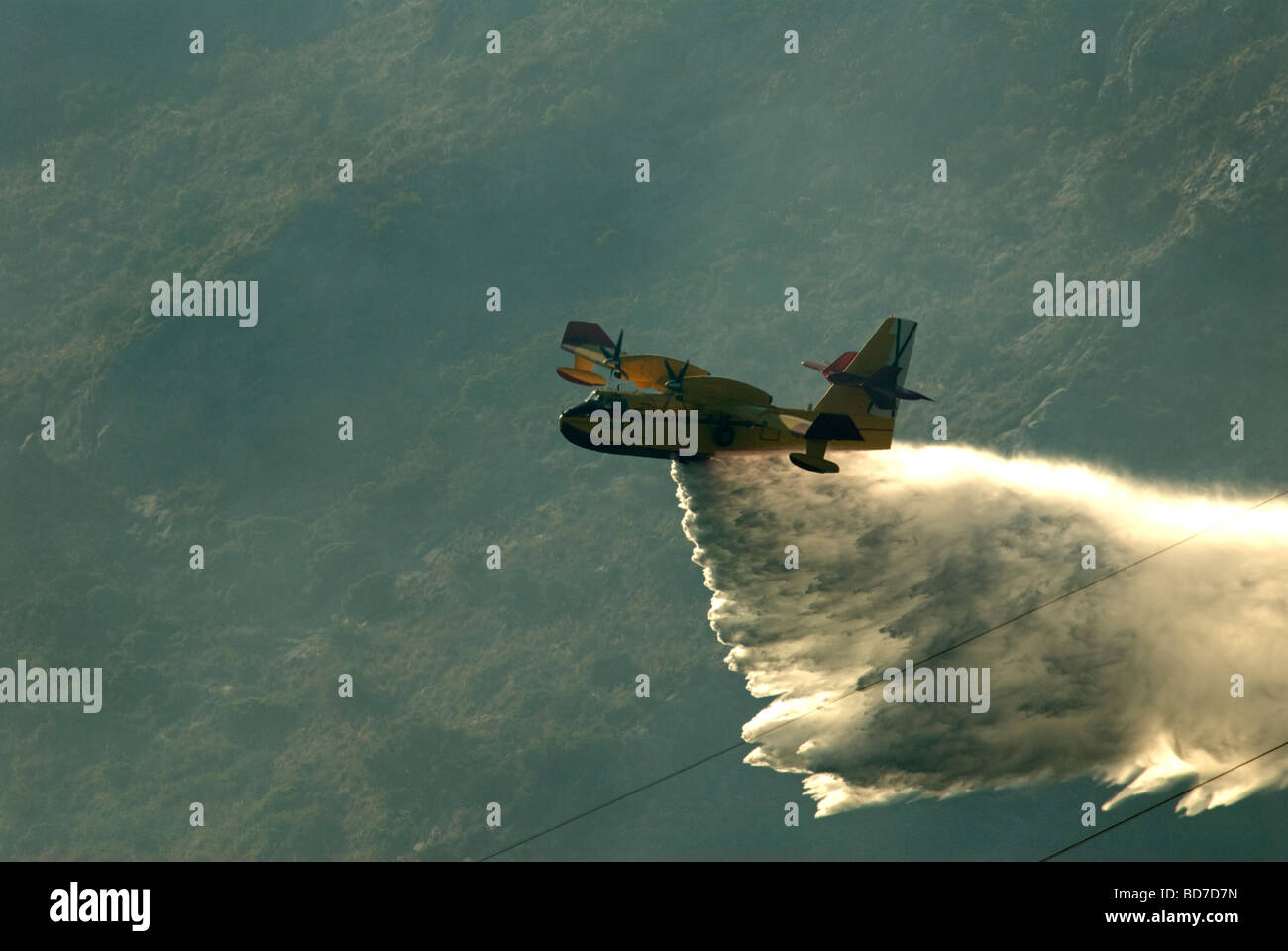 Twin engined Canadian firefighting aircraft dropping water onto forest fire - Stock Image