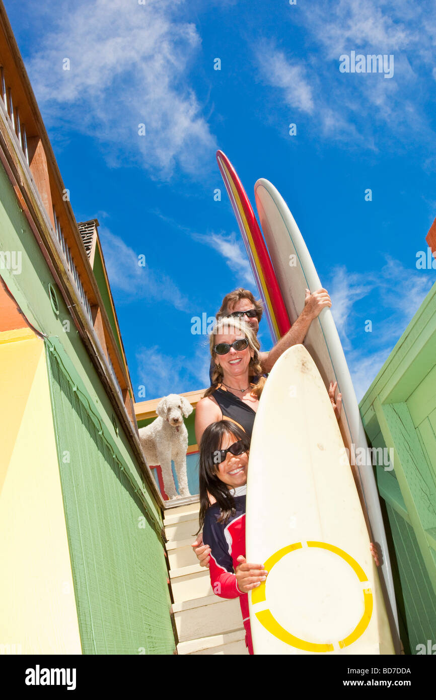Family with surfboards on stairs - Stock Image