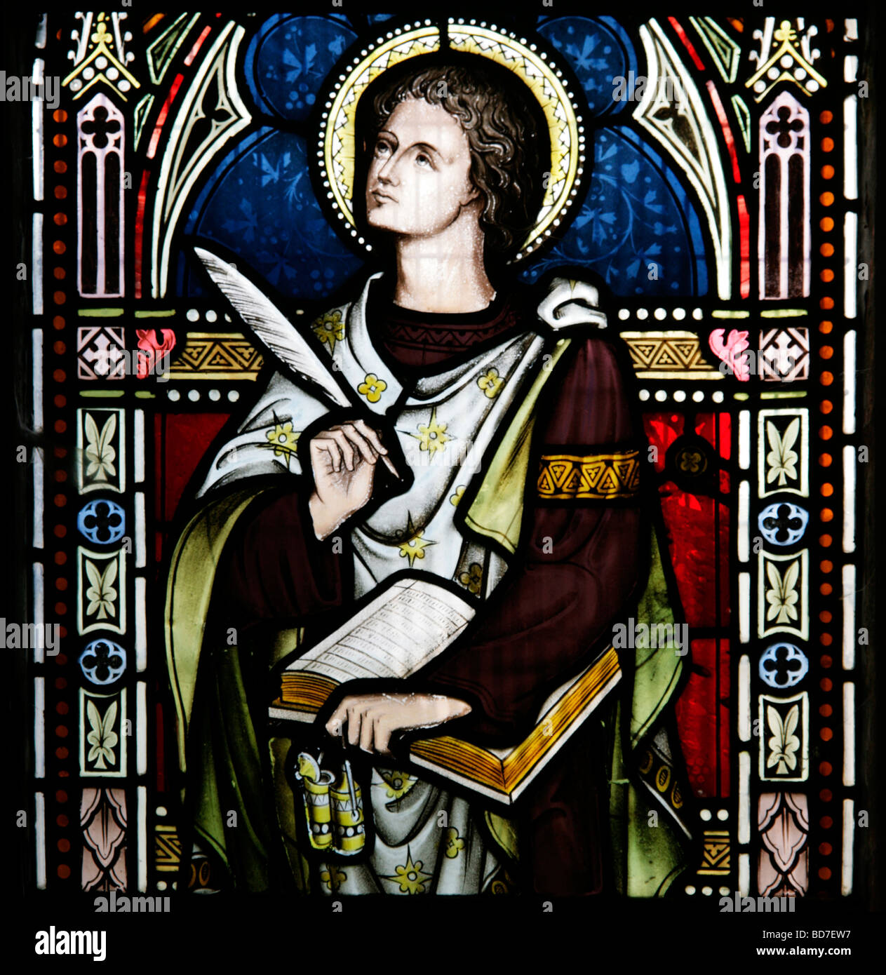 A Stained Glass Window depicting Saint John holding a book and quill - Stock Image