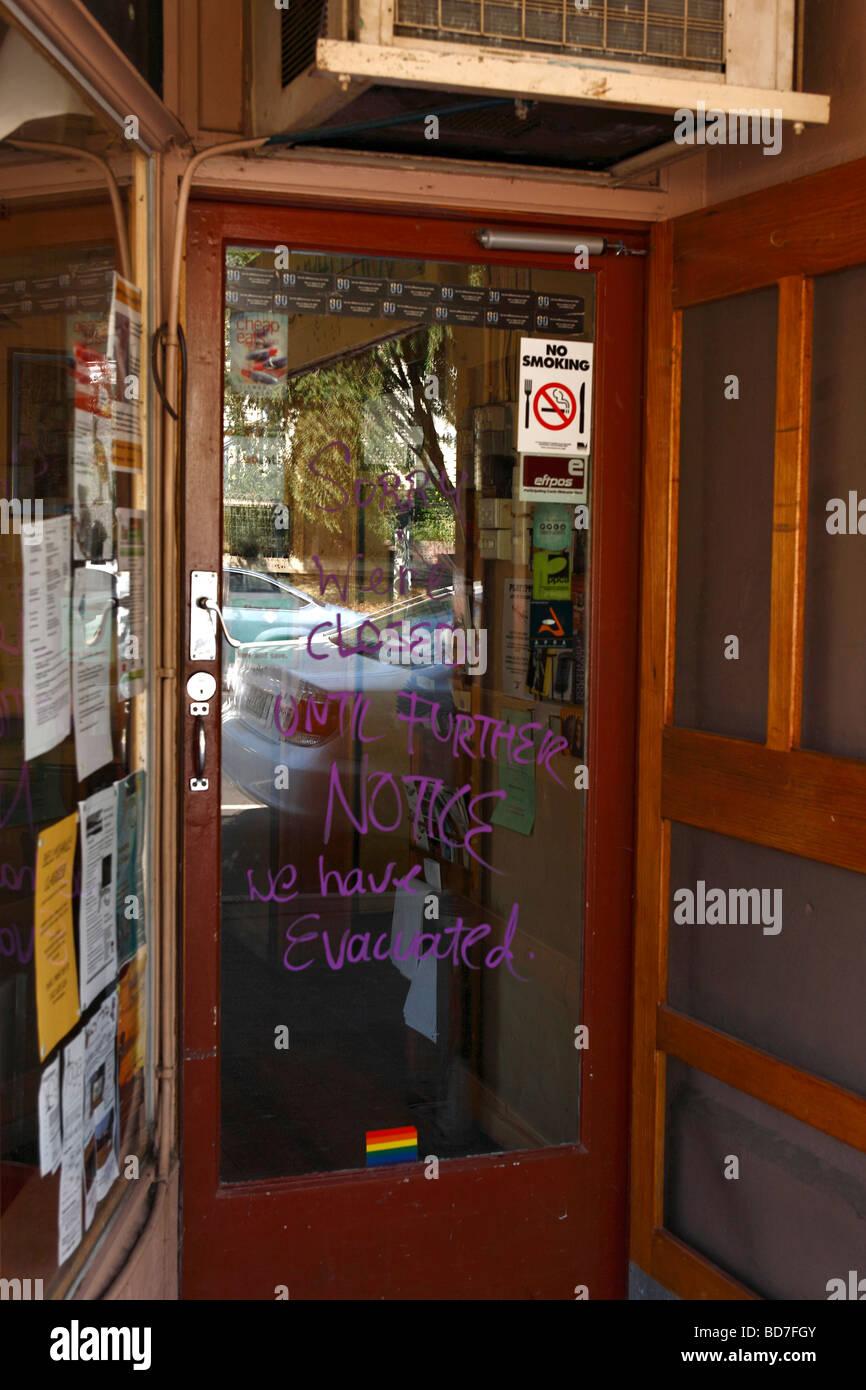 Hand written fire evacuation notice on glass shop door Warburton Victoria Australia - Stock Image