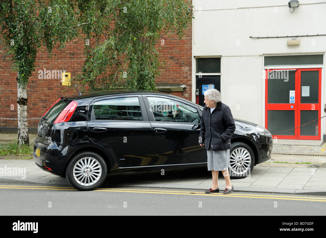 Elderly lady walks out into road as pavement is blocked by car Holloway London England UK - Stock Image