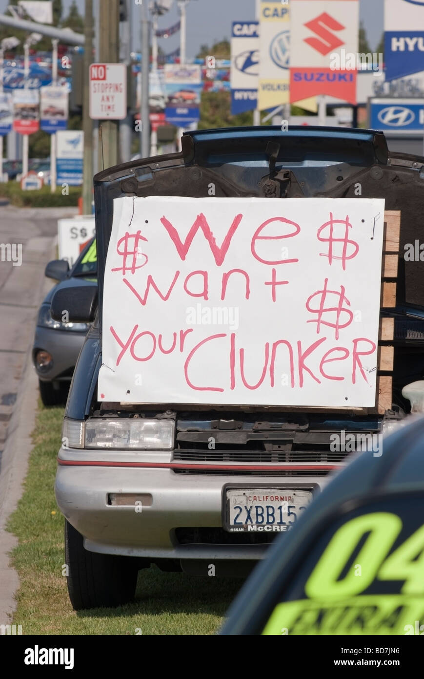 Cash-for-Clunkers, a 1996 Chevrolet outside of an Auto dealership advertising the U.S. Government Auto trade in - Stock Image