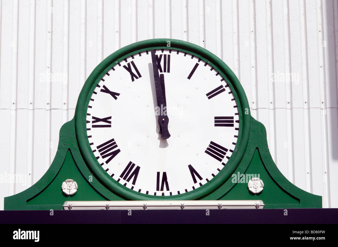 Large green and white restored 'cricket pavilion' clock displaying 'one minute to noon' - Stock Image