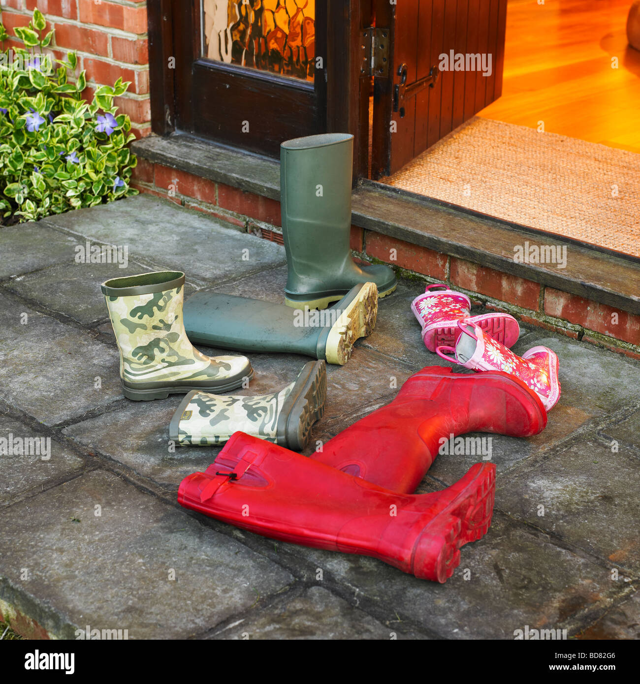 A rush to get home, a families wellington boots left outside the front door. - Stock Image