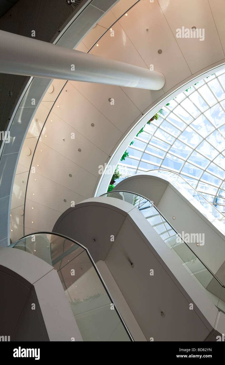 Interior shot of a building showing the lines of the modern architectural design leading up to a glass domed roof - Stock Image