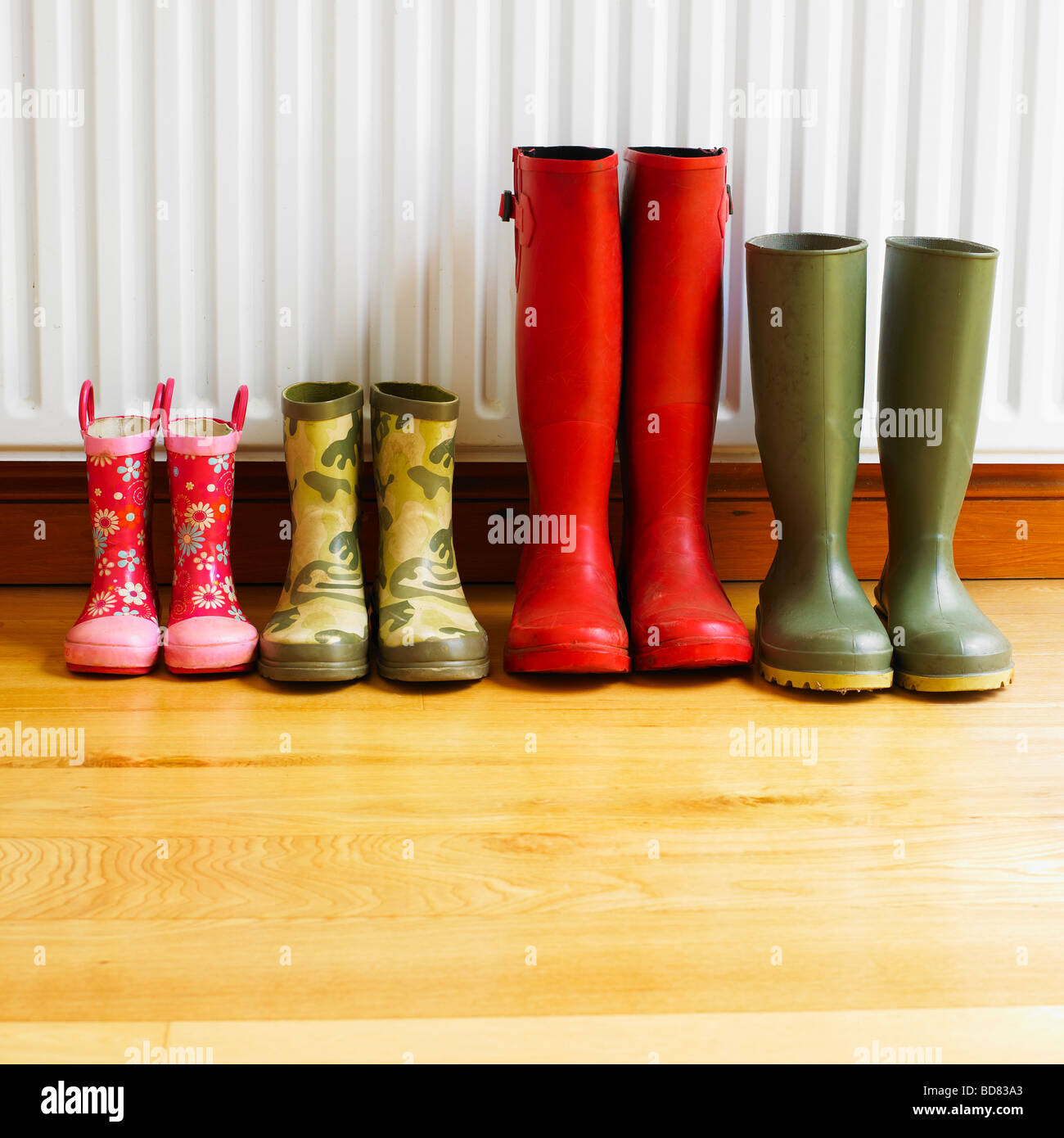 A family's Wellington boots drying in front of a radiator. - Stock Image