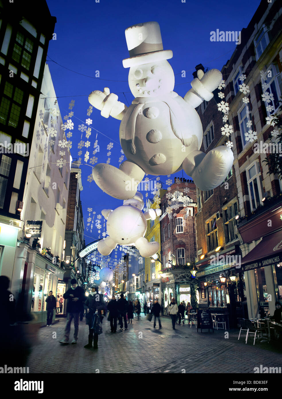 Christmas decorations, including giant inflatable snowmen, lit up at night in Carnaby Street, in London's West - Stock Image