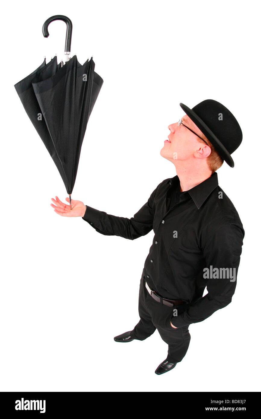 young man with bowler hat balancing an umbrella - Stock Image