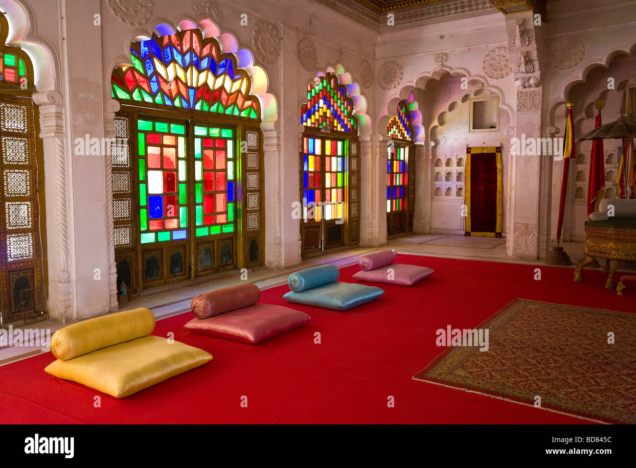 Gaudy room in the palace at Jodhpur with carved stonework and coloured glass above a red carpet and colourful cushions - Stock Image