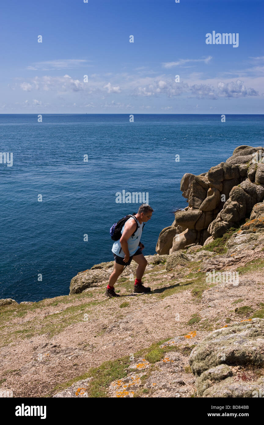 A rambler walking along the coastal path in Cornwall.  Photo by Gordon Scammell - Stock Image