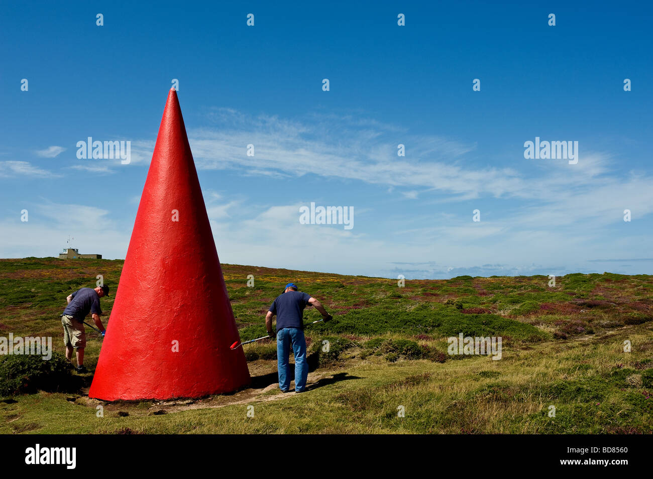 Workmen painting one of the navigation markers near Porthgwarra in Cornwall. - Stock Image