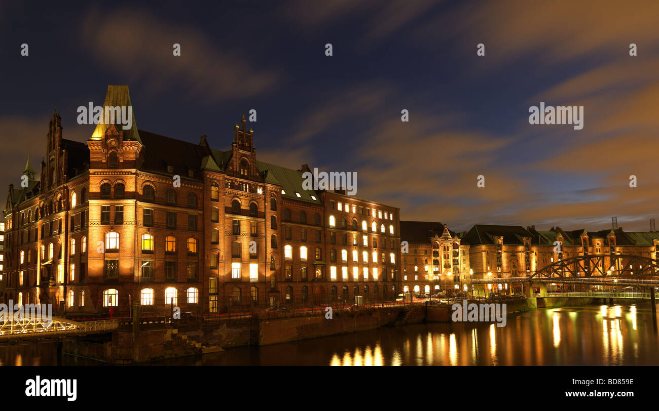 The historic warehouse district of Hamburg, northern Germany under a cloudy sky at the blue hour on Saturday February - Stock Image