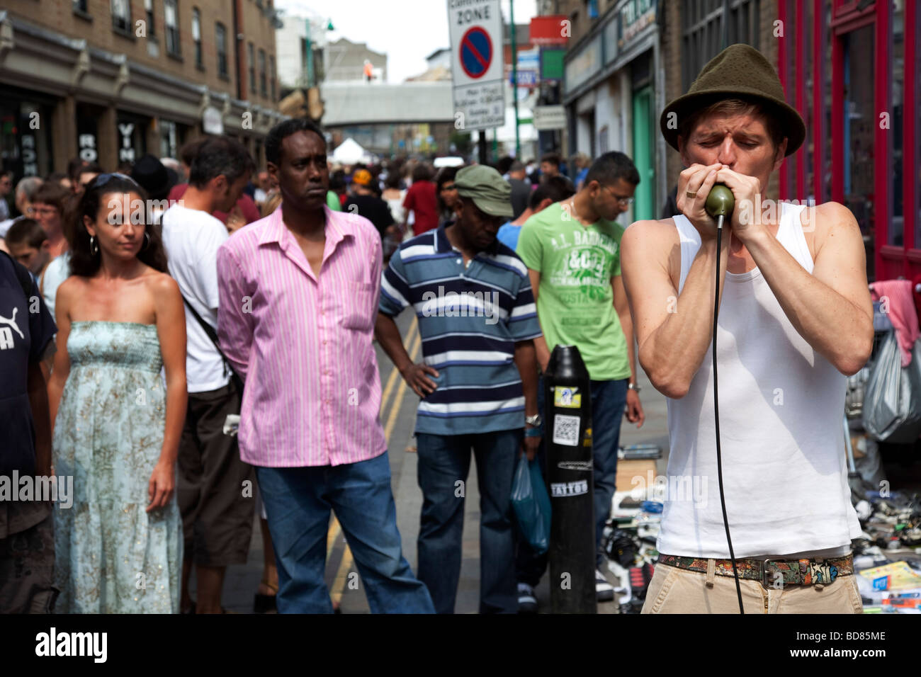 Harmonica player entertains the crowds at Brick Lane Market. This market is a weekly event on Sunday in London s - Stock Image