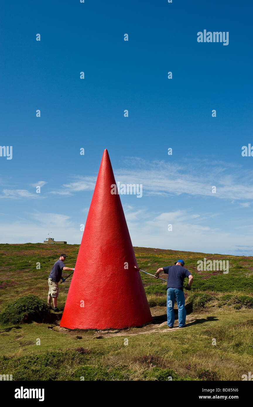 Workmen painting a navigation marker near Porthgwarra in Cornwall. - Stock Image