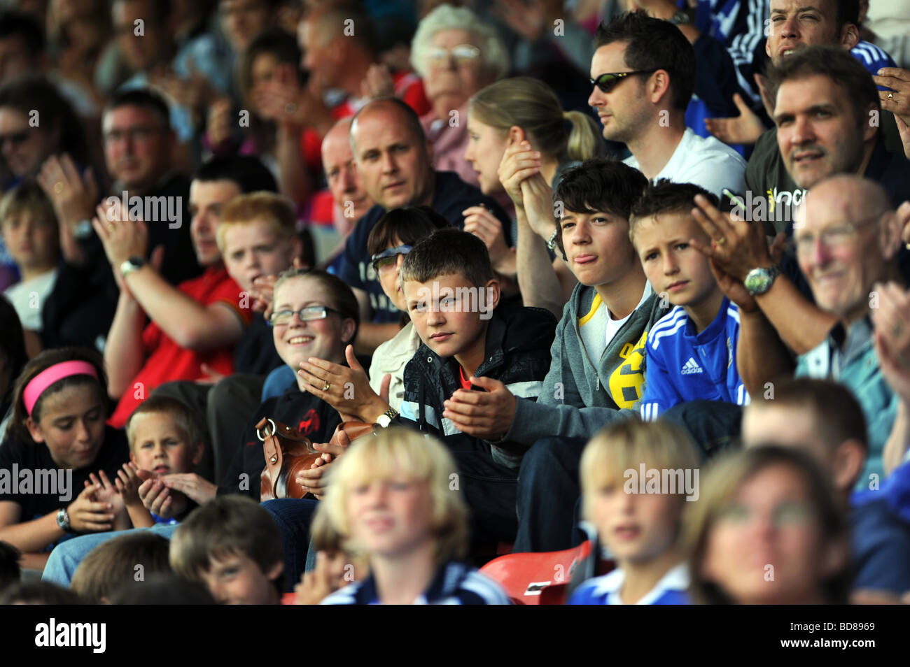 Young faces in the crowd at a football match - Stock Image