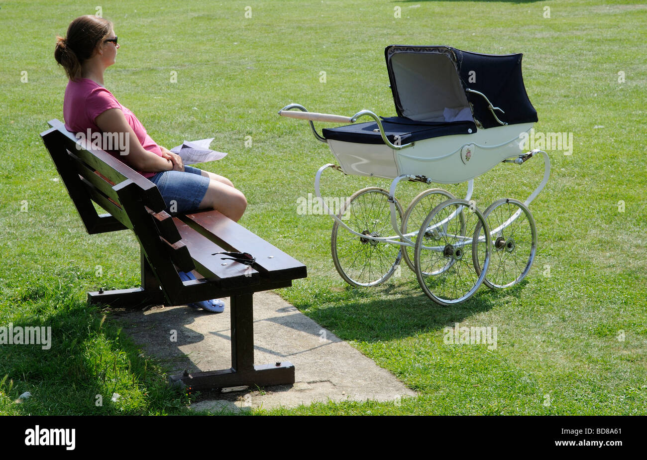 Woman Sitting On A Park Bench With An Old Fashion Style Pram Stock