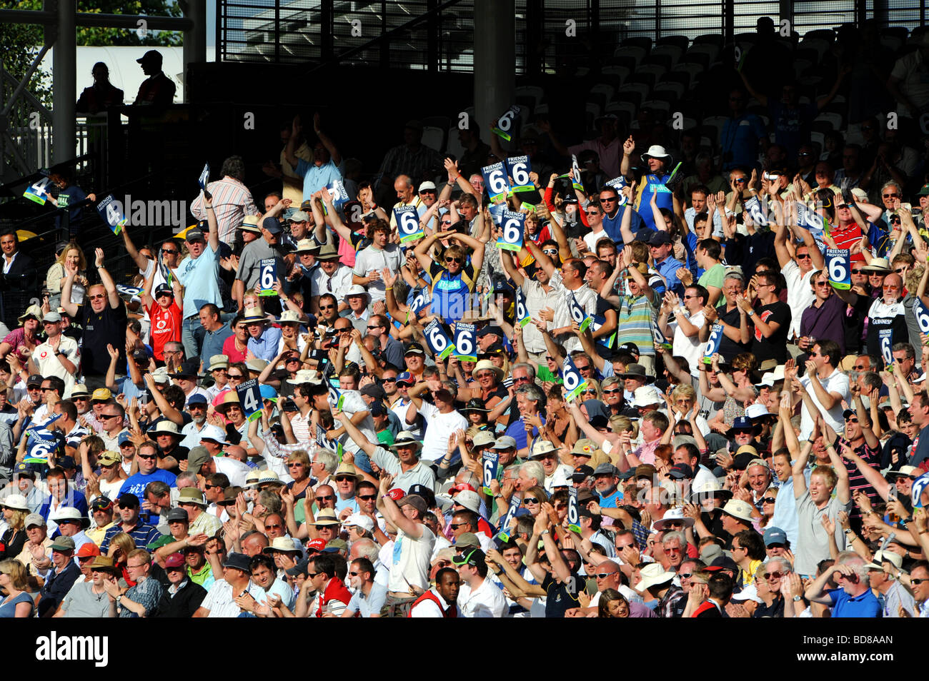 Members of the crowd at a cricket match at lord's hold up some six signs - Stock Image