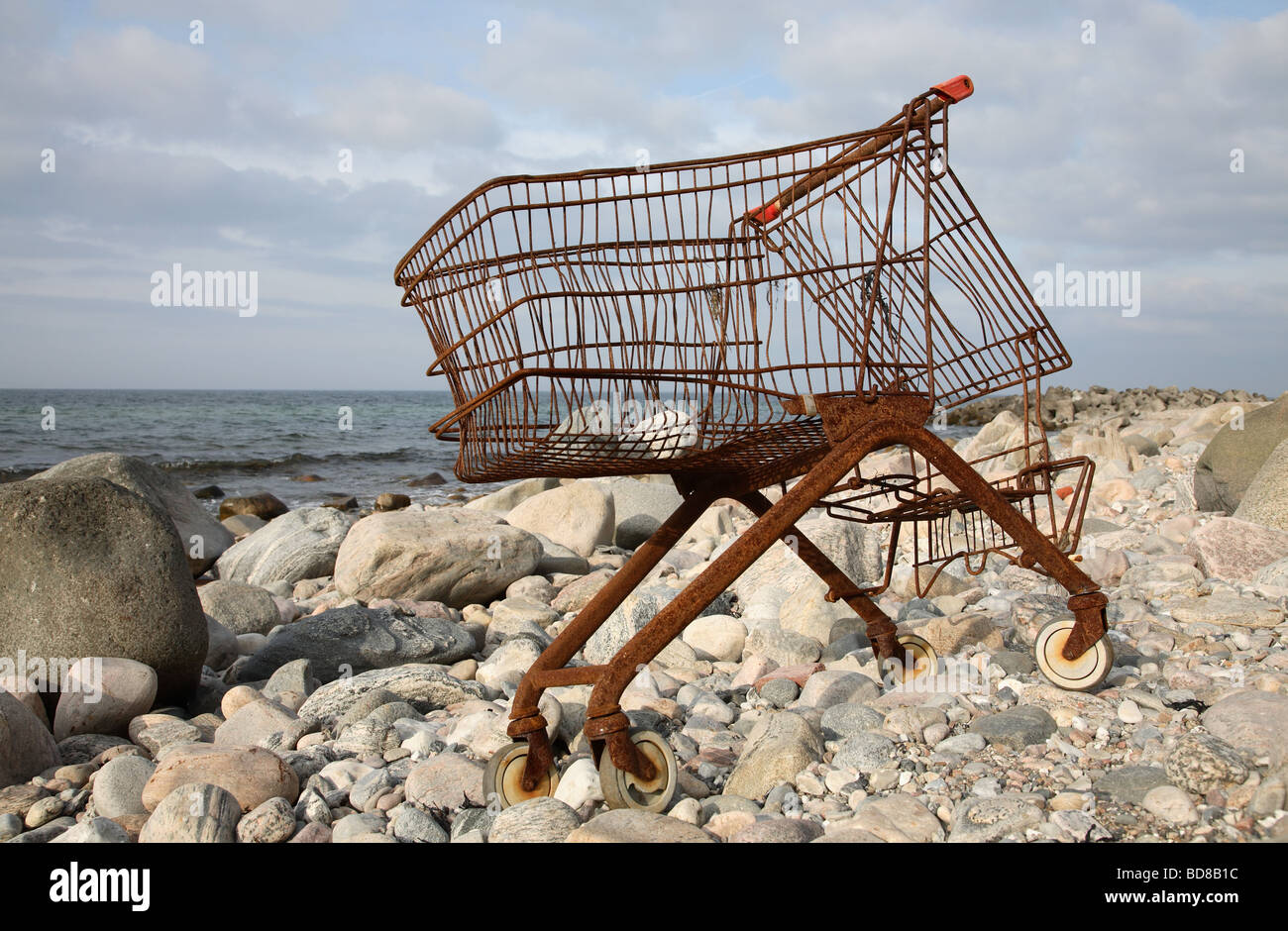 The last shopping - rusty shopping cart on a desolate and rocky beach. - Stock Image