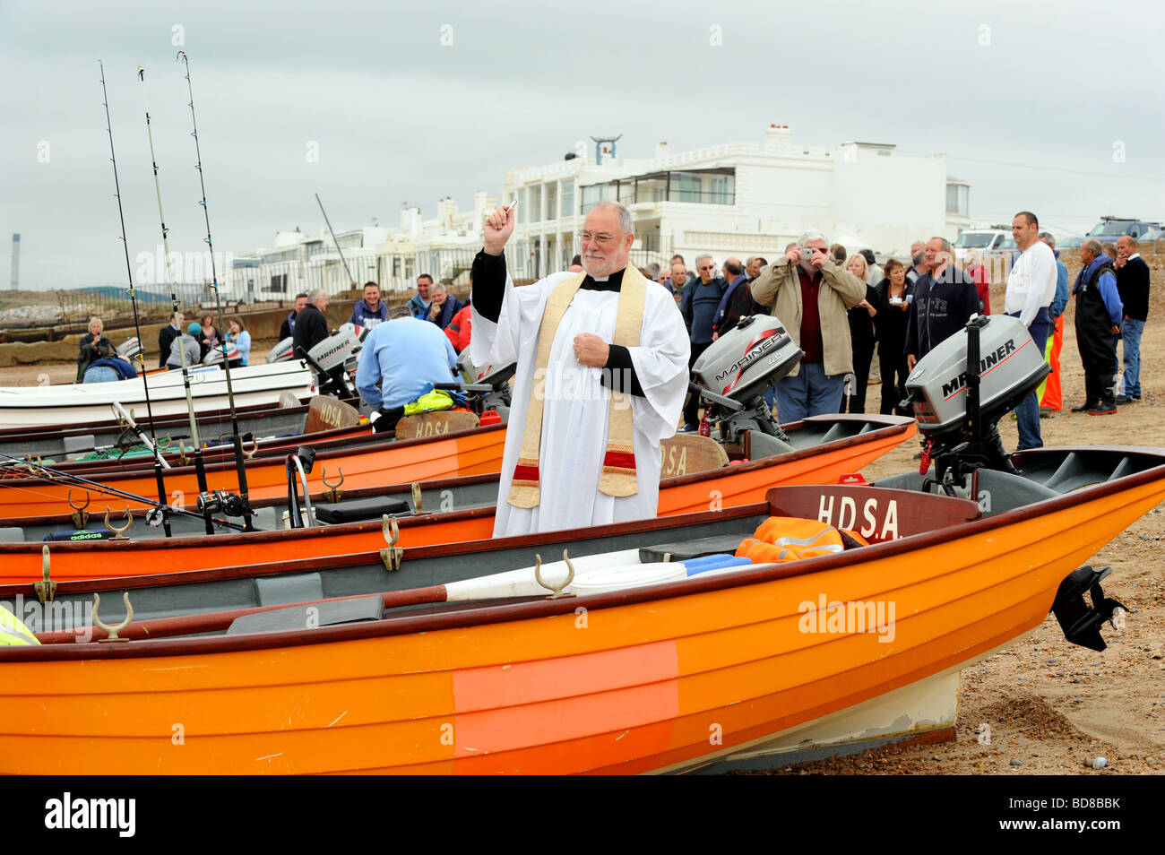 A vicar blesses fishing boats on Brighton beach before they go out - Stock Image