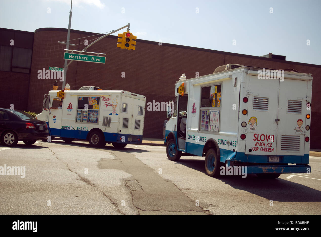 A Mr Softee truck followed by a soft ice cream competitor in the borough of Queens in New York - Stock Image