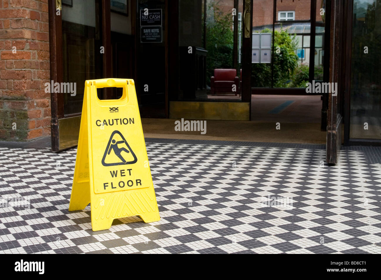 A hotel entrance with a wet floor slippery surface danger sign - Stock Image
