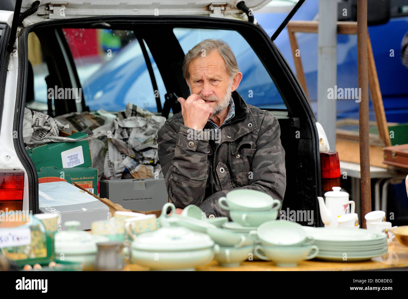 A dealer waits to sell his goods at the Brighton station car boot sale - Stock Image