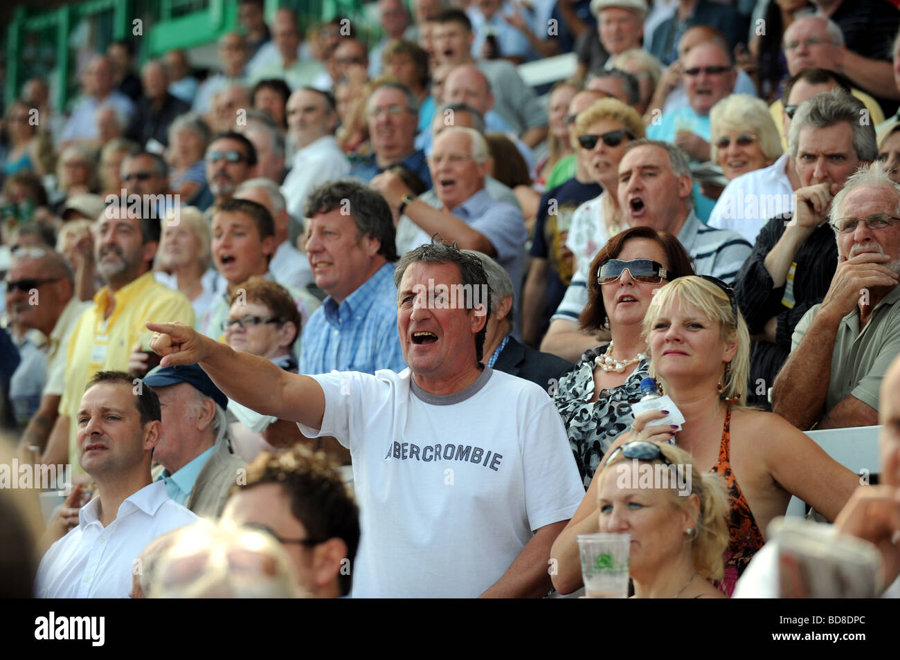 Racegoers at Brighton Races cheering on the runners and riders UK - Stock Image