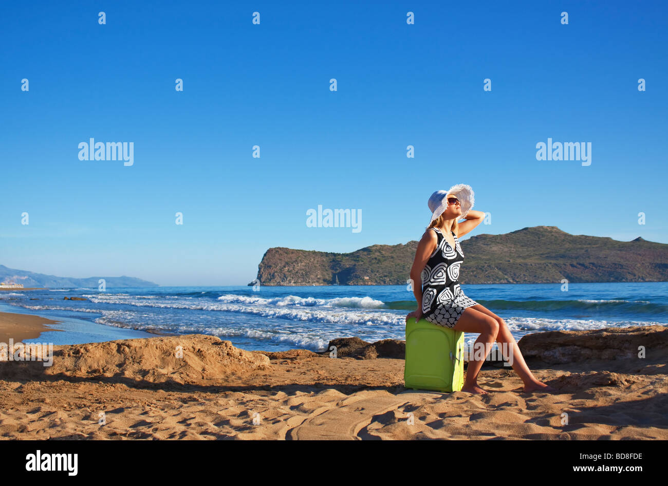 Young blond Caucasian woman wearing white straw hat and sunglasses sitting on green suitcase on a beach - Stock Image