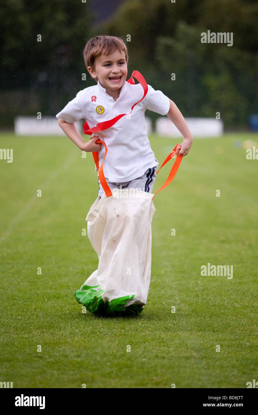 Boy in sack race on grass field on school sports day - Stock Image