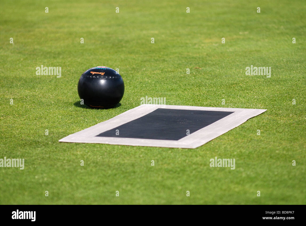 A lawn bowls mat and ball on the lawn - Stock Image