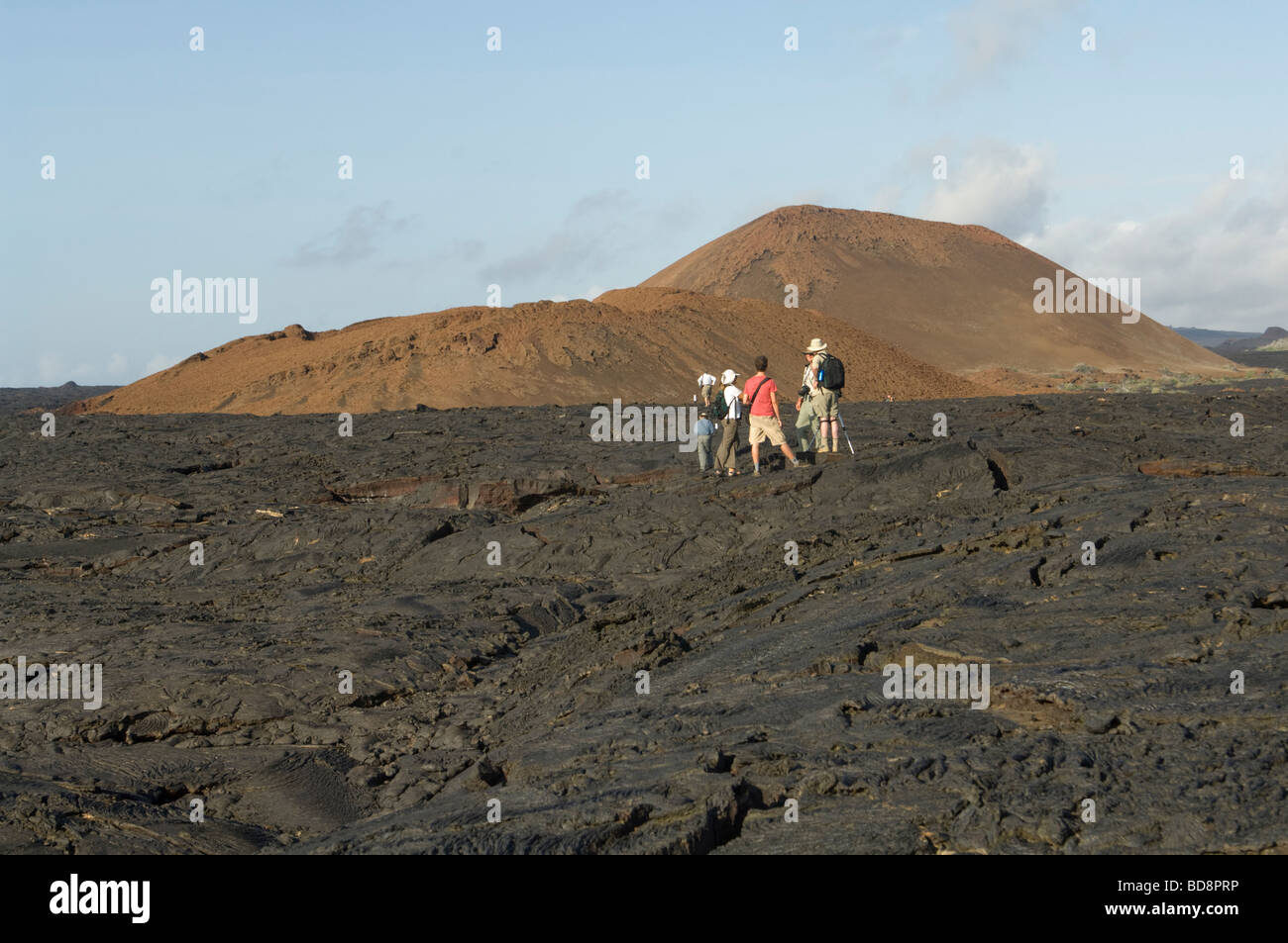 Group of tourists standing on lava field volcanic cone on the background  Sullivan Bay Santiago Island Galapagos - Stock Image