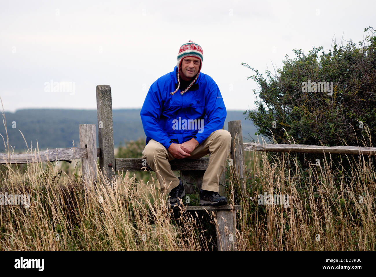 A man with a woolly hat sits and rests on a Stile - Stock Image