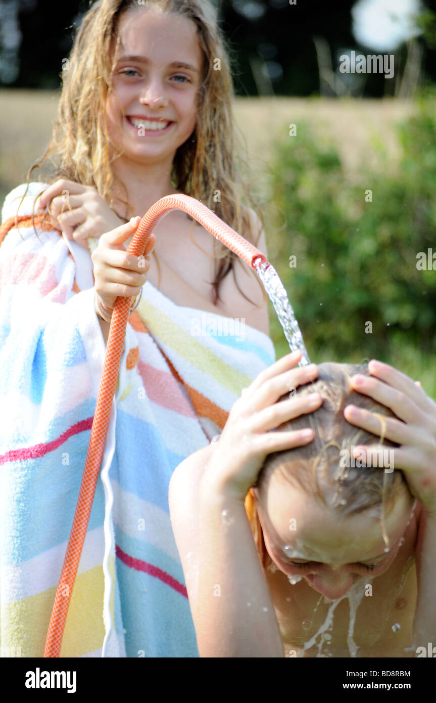 photograph of a girl washing and cooling with hose pipe water on a