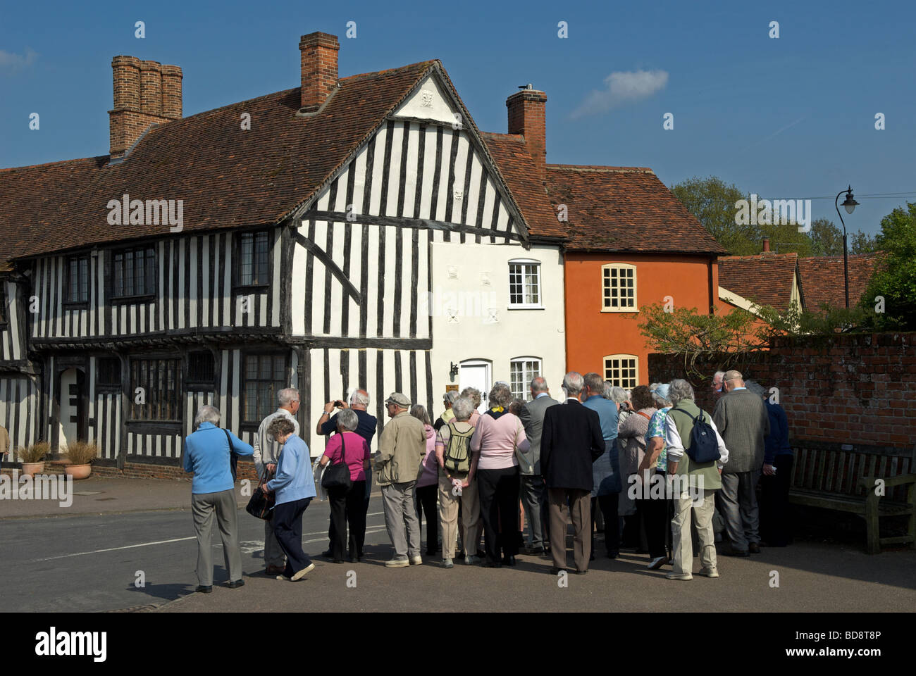Group of tourists on a tour of Lavenham, Suffolk, UK. Stock Photo