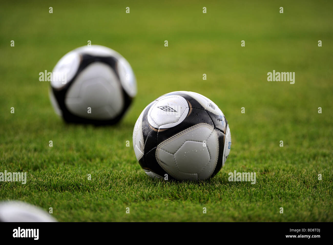 Two footballs on a football pitch - Stock Image