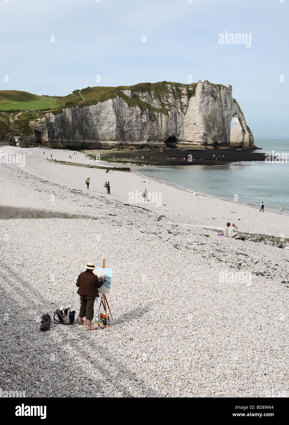 An artist making a painting of the cliffs including the Falaise d'Aval or arch and the Aiguille or needle at - Stock Image