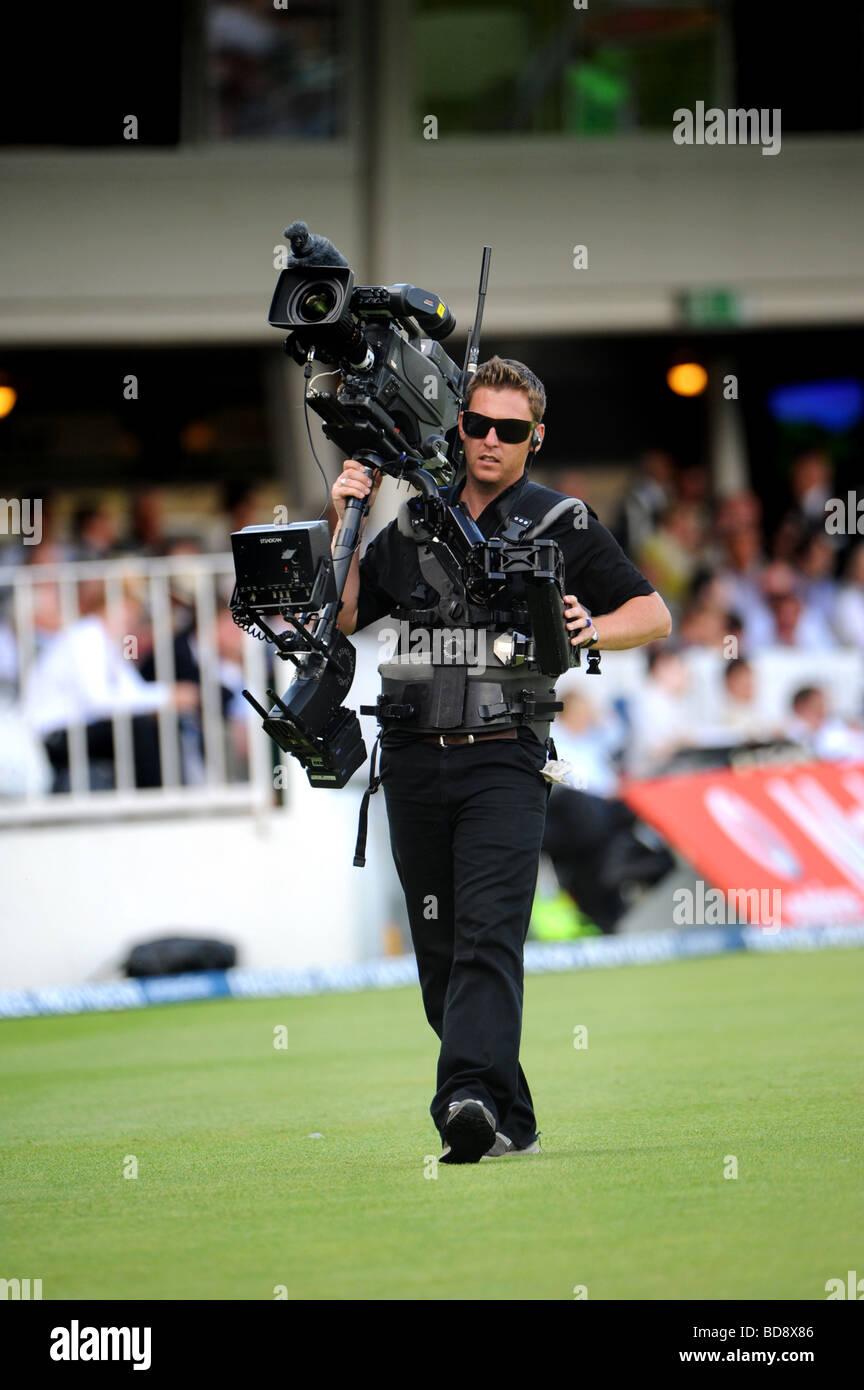 A tv cameraman at a televised cricket match - Stock Image