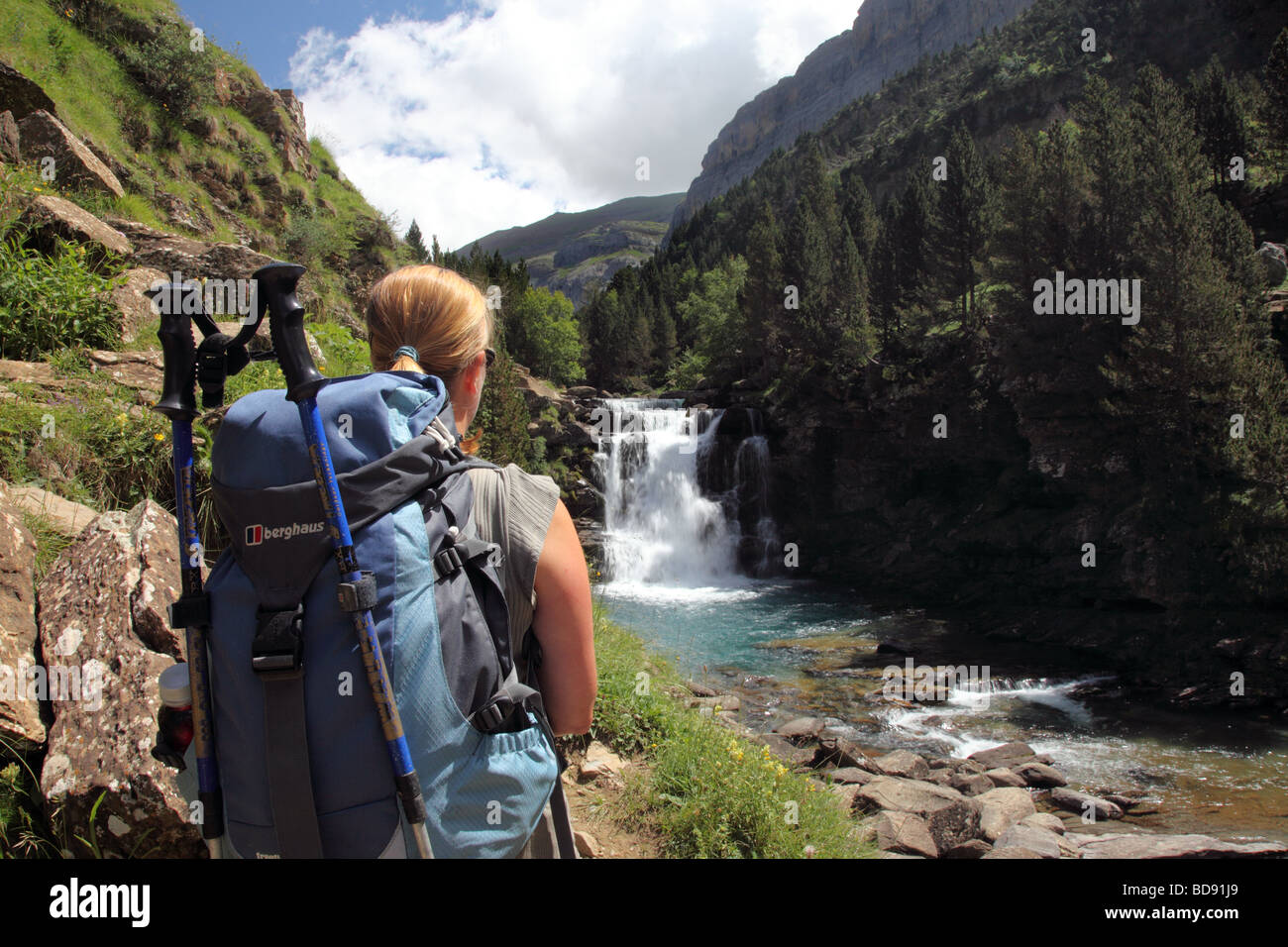 Female Hill Walker on the GR11 Footpath Enjoying the View of a Cascade on the Rio Arazas in the Ordesa Canyon Pyrenees - Stock Image