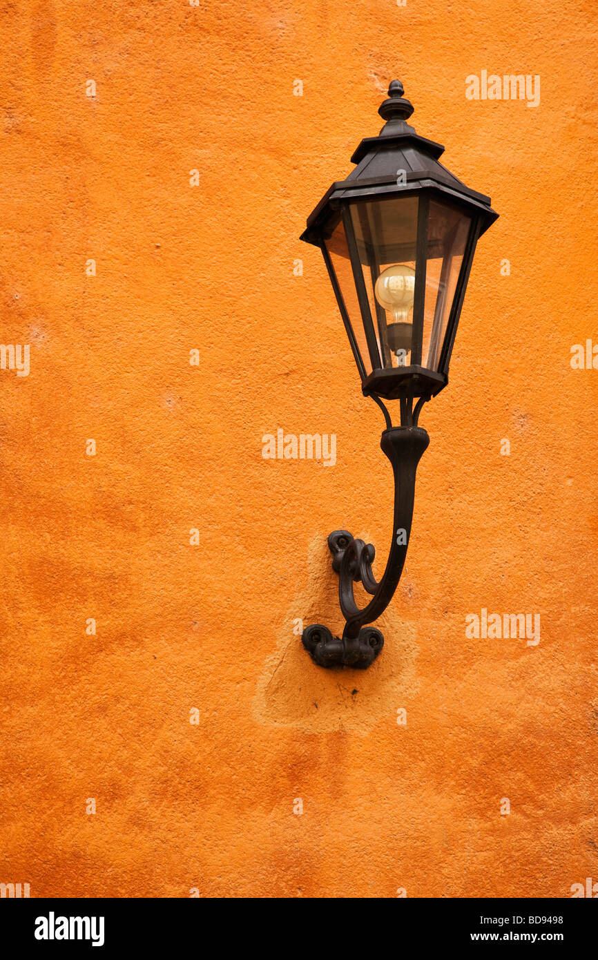 Old style city street lighting lamp on a terracotta wall - Stock Image
