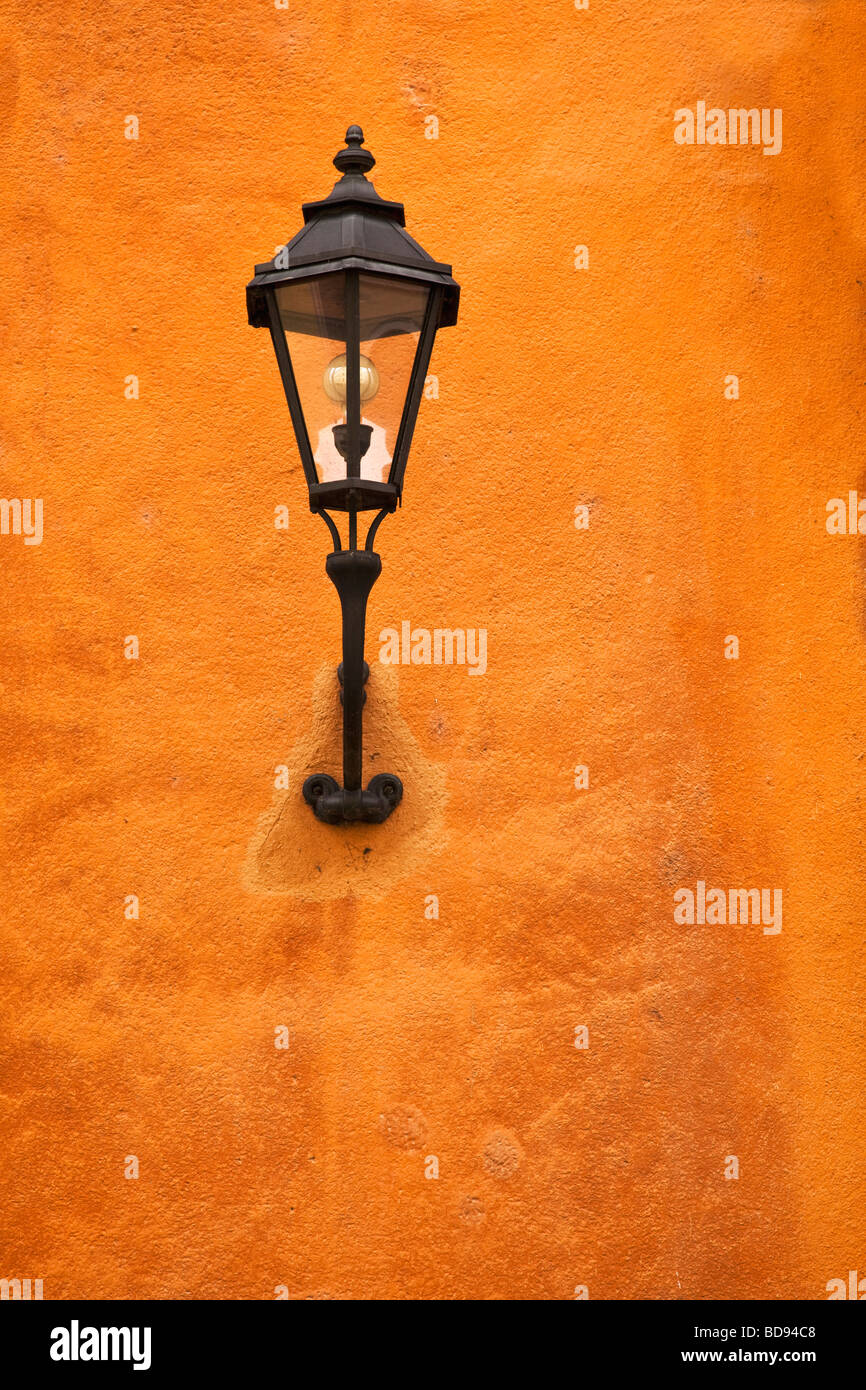 Traditional wall-mounted old style city street lamp on a terracotta wall - Stock Image