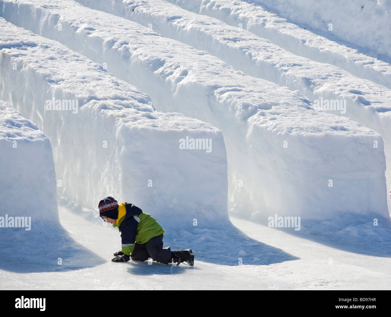 a9df43e4e8f0 After the Slide. A young boy tries to stand up on the slippery ice just